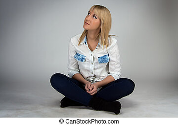 Image of woman sitting on floor and looking up