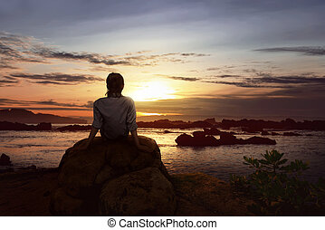 Image of woman sitting on the rock