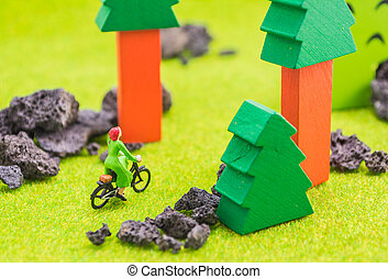 image of woman(mini figure dolls) with retro bicycle alone in a park.