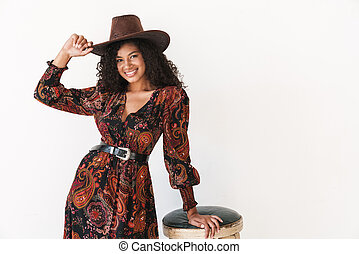 Image of young african american cowgirl in dress and hat standing by chair
