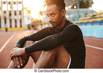 Image of young african american man sitting at sports ground outdoors