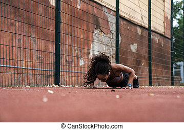 Image of young african american woman doing push-ups at playground