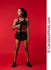 Image of young african american woman in black sportswear lifting dumbbell, isolated over red background