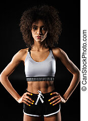 Image of young african american woman posing with hands on waist