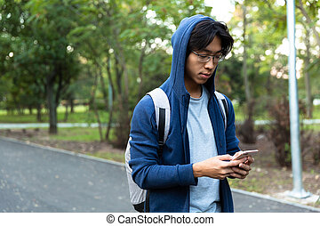 Image of young asian guy in casual wear and eyeglasses using smartphone, while walking through green park