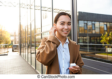 Image of young brunette asian woman using earbuds on city street