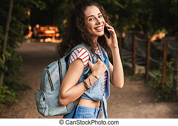 Image of young brunette student 18-20 wearing backpack, smiling while walking through green park and speaking on mobile phone