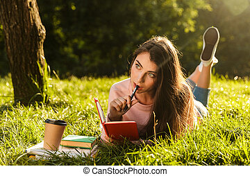 Image of young brunette woman thinking and writing down notes in diary while lying at grass in green park
