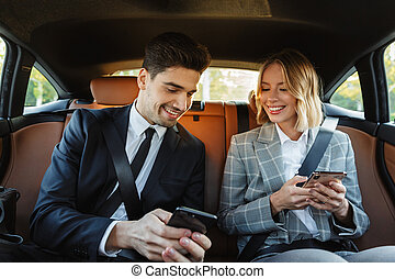 Image of young businesslike man and woman using smartphones ...