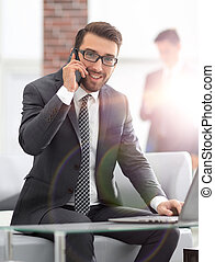 image of young businessman talking on mobile phone with clients