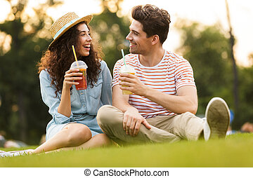 Image of young couple man and woman 20s sitting on green grass in park, and drinking beverages from plastic cups