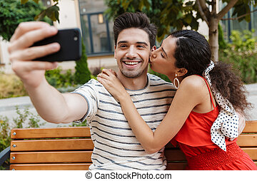 Image of young couple taking selfie photo on cellphone and kissing