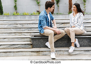 Image of young couple talking and smiling while sitting on bench near stairs outdoors