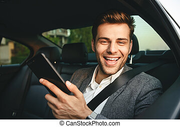 Image of young director man in suit holding smartphone and smiling, while back sitting in business class car with safety belt