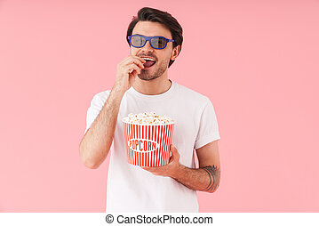 Image of young funny man wearing 3d glasses eating popcorn while watching movie