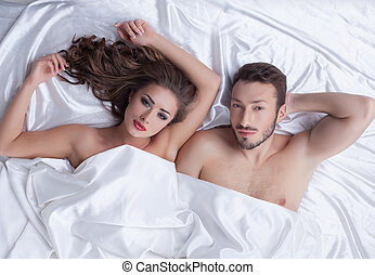 Image of young heterosexual couple posing in bed, close-up