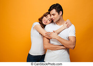 Image of Young lovely couple posing together and hugging