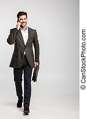 Image of young smiling businessman talking on cellphone while walking with bag