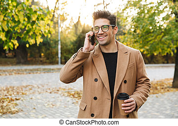 Image of young smiling man wearing coat talking on cellphone and drinking takeaway coffee in autumn park