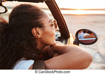 Image of young thoughtful woman looking aside while riding in convertible stylish car by seaside