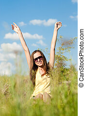 image of young woman beautiful girl sitting in grass happy smiling having fun hands up & looking at camera on green summer outdoor blue sky copy space background portrait