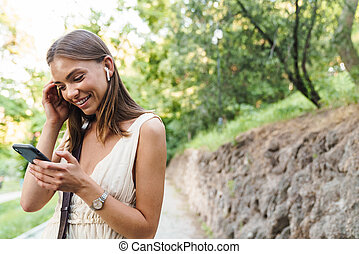 Image of young woman in earbuds laughing and holding ...