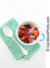 Image on top of oatmeal with raspberries, strawberries, blackberries on table