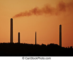 Image with orange tint to highlight the impact of industrial chimney stacks polluting the air in a natural landscape setting