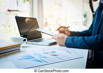 Images of Business man working at office with laptop and documents on his desk. Analyze plans, papers, hands keyboard, blurred background
