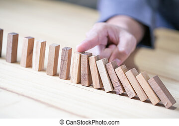 Images of hand stopping domino effect with his finger. Business crisis concept.