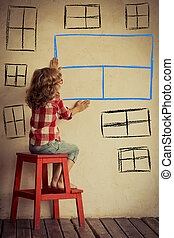 Sad child sitting against old wall with drawn window. Freedom and imagination concept