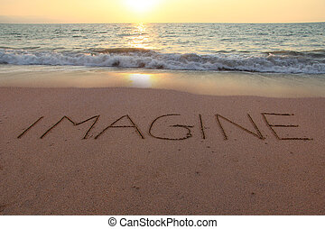 Imagine written in the sand on a sunset beach.