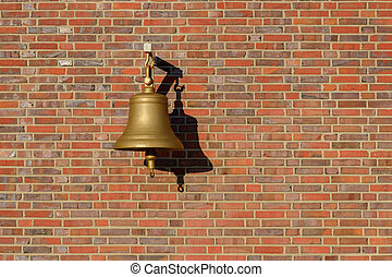 bell hanging on a brick wall