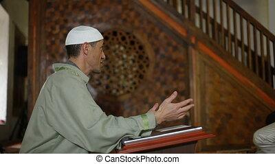 Imam preaching in a mosque - Imam, islamic priest praying in...