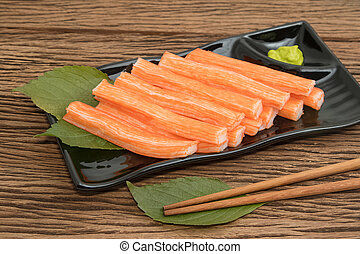Imitation Crab Stick in plate on wooden background
