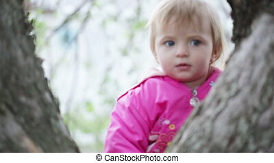 Immediate child - Year-old girl peeking out from behind a...