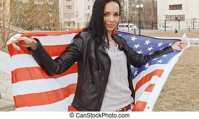 Latino girl with wavin United States flag in hands behind...