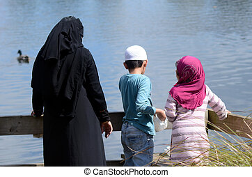 Immigrants muslim family feed ducks in a pond