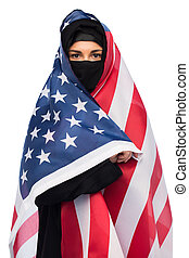 muslim woman in hijab with american flag - immigration and...