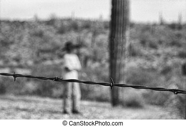 Barb wire and boy symbolizing immigration