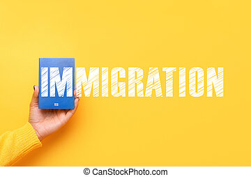 blue passport in hand over yellow background,  immigration concept