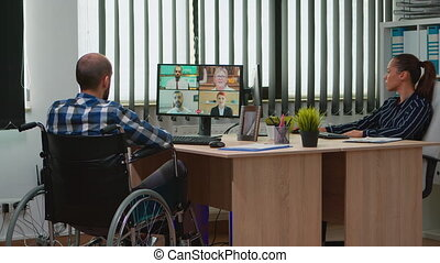 Paralysed, immobilized freelancer in wheelchair having videomeeting discussing online with coworkes in business office. Handicapped businessman working in financial company using modern technology.