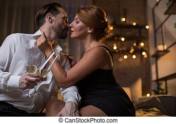 Impassionate man and woman drinking champagne on bed