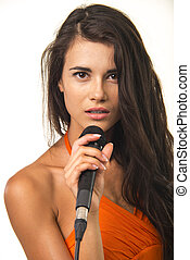 Impassioned girl in orange shirt with microphone.