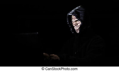 Impatient angry male hacker wearing hood in a dark room cracking digital labyrinth data while the image is projected on his face