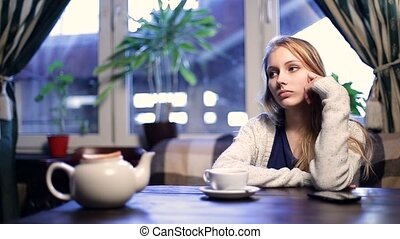 Impatient girl waiting for her boyfriend in cafe