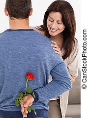 Impatient woman looking at a flower hidden by her boyfriend