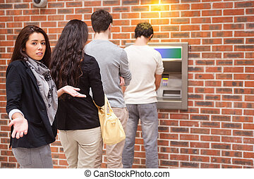 Impatient woman queuing at an ATM