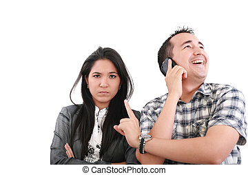 Impatient woman standing with arms crossed looking at his boyfriend listening on the mobile phone