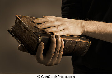 Important Book - Toned image of a Man holding an old book in...
